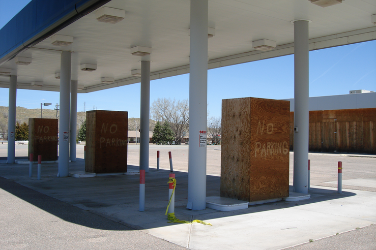 No Parking Signs Overshadow Boarded Up Convenience Store